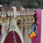 Indian stuntman Sailendra Nath Roy is watched by onlookers as he hangs on a rope while attempting to cross the River Teesta on the outskirts of Siliguri on April 28, 2013.   A dare-devil Indian who held the Guinness World Record for covering the longest distance on a zip-line while hanging by his hair has died while performing a stunt, officials said April 29. Sailendra Nath Roy, a 49-year-old police officer, was attempting to cross the turbulent river Teesta in the state of West Bengal on a 180-metre (600-foot) wire hanging above the water.    AFP PHOTO/Diptendu DUTTA        (Photo credit should read DIPTENDU DUTTA/AFP/Getty Images)