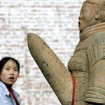 A visitor looks at a terracotta warrior sculpture in Beijing